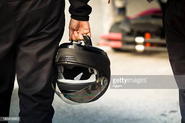 Race driver holds a helmet on the track