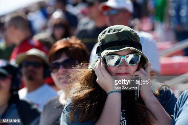 A race fan covers her ears during the Monster Energy NASCAR Cup Series Kobalt 400 race on March 12 at the Las Vegas Motor Speedway in Las Vegas NV