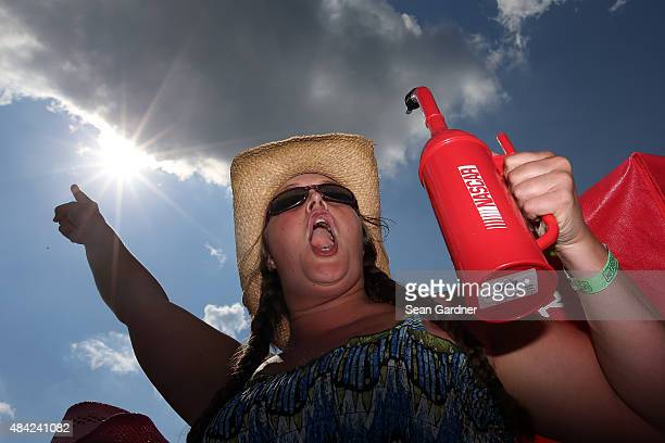 A race fan enjoys the action during the NASCAR Sprint Cup Series Pure Michigan 400 at Michigan International Speedway on August 16 2015 in Brooklyn...