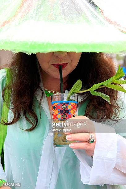A race fan in a festive hat enjoys a mint julep while it rains prior to the 139th running of the Kentucky Derby at Churchill Downs on May 4 2013 in...