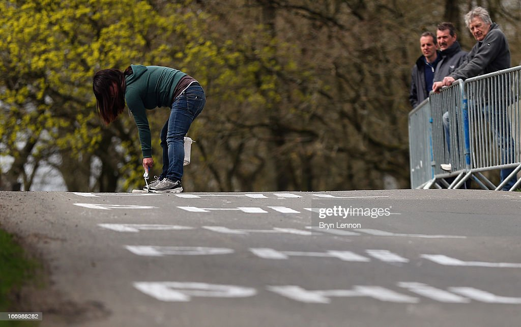 A race fan paints the road with the name of World Road Race Champion Philip Gilbert during training for the 99th Liege-Bastogne-Liege cycle road race on April 19, 2013 in Liege, Belgium.