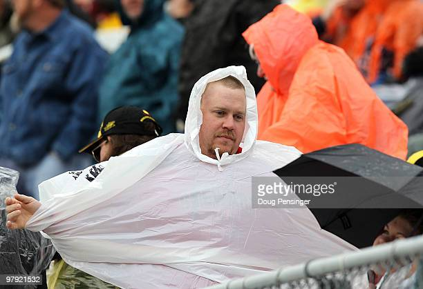 A race fan puts on a poncho during rain caution in the NASCAR Sprint Cup Series Food City 500 at Bristol Motor Speedway on March 21 2010 in Bristol...