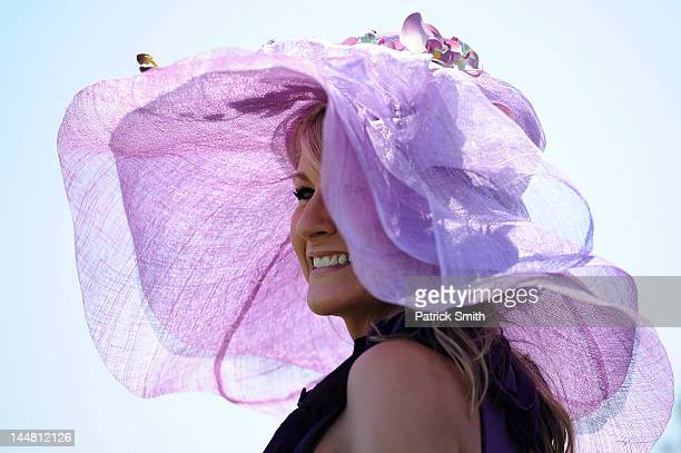 A race fan sports a big purple hat prior to the 137th running of the Preakness Stakes at Pimlico Race Course on May 19 2012 in Baltimore Maryland