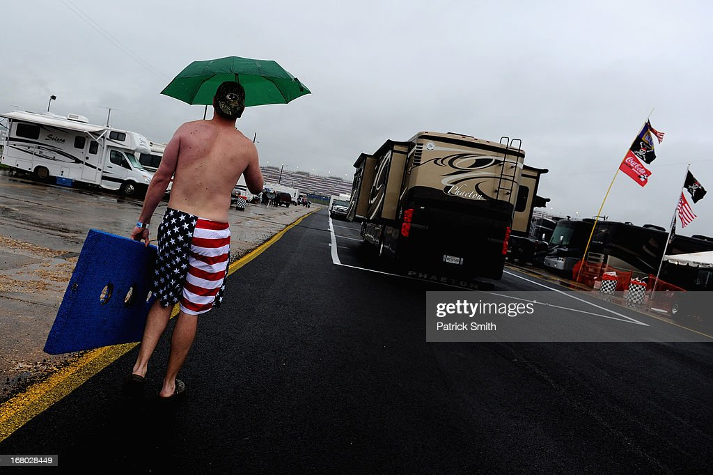 A race fan walks with an umbrella past campers and haulers parked on the infield during qualifying for the NASCAR Sprint Cup Series Aaron's 499 at Talladega Superspeedway on May 4, 2013 in Talladega, Alabama. Qualifying was canceled due to inclimate weather.