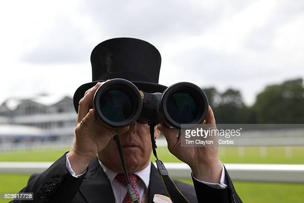 A race goer looks through a pair of binoculars during the race meeting at Royal Ascot Race Course Royal Ascot is one of the most famous race meetings...