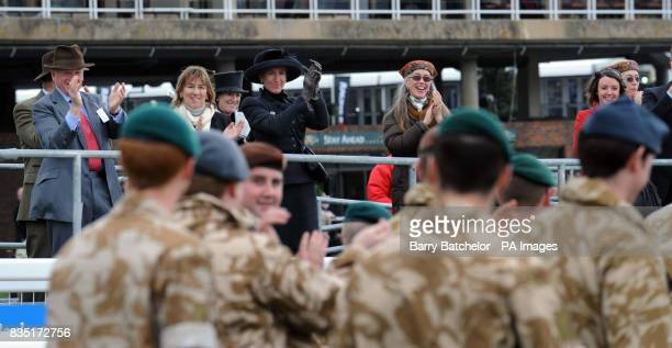 Race goers applaud and cheer serving personnel who have recently returned from overseas duties as they parade in support of the British Forces...