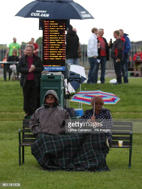 Race goers shelter from the rain at York Racecourse York