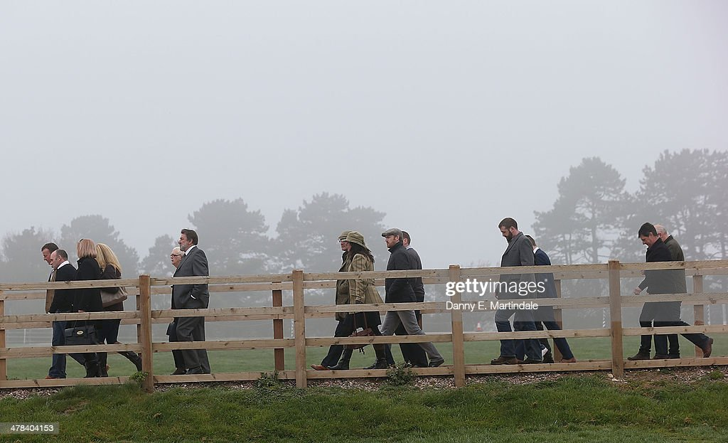 Race goers walk to the racecourse in the fog on day 3 of The Cheltenham Festival at Cheltenham Racecourse on March 13, 2014 in Cheltenham, England.