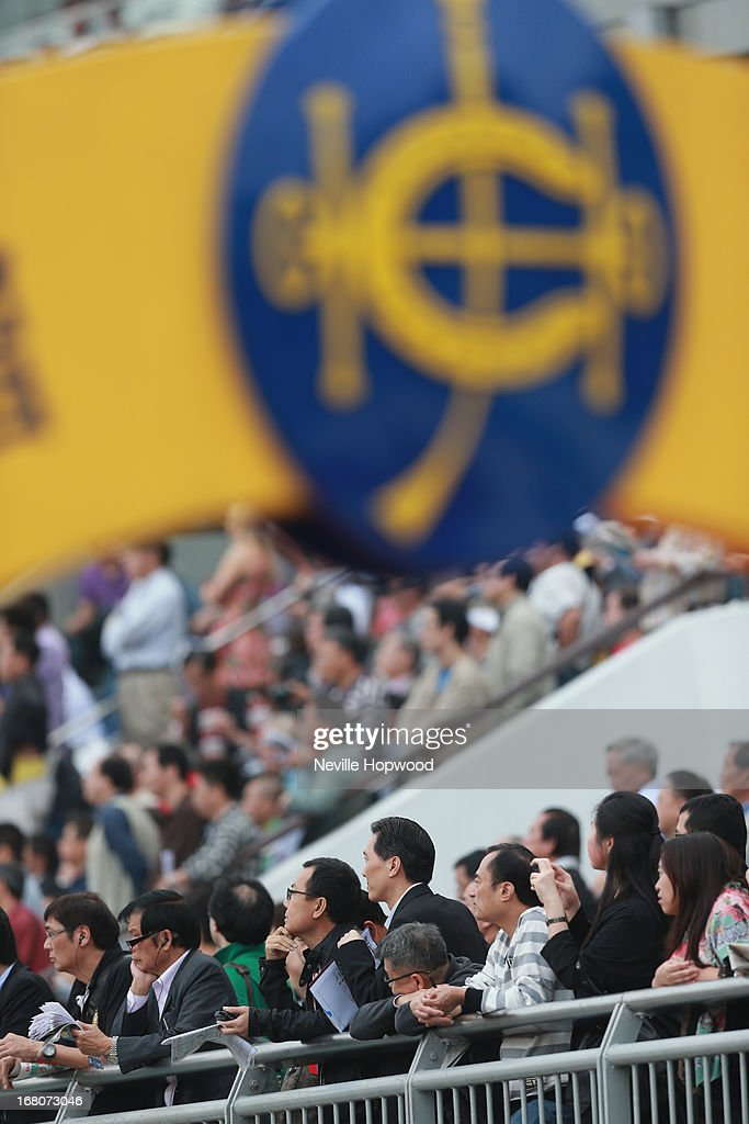 Race goers watch the action during The Champions Mile during The Champions Mile meeting at Sha Tin racecourse on May 5, 2013, in Hong Kong, Hong Kong.