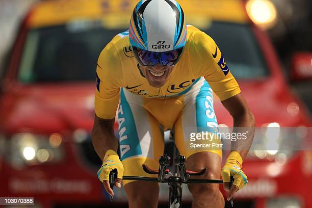 Race leader Alberto Contador of team Astana crosses the finish line in the yellow jersey following stage 19 of the Tour de France on July 24 2010 in...