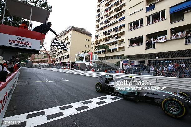 A race marshal waves the end of race black and white checkered flag as Mercedes AMG Petronas F1 Team's German driver Nico Rosberg crosses the finish...