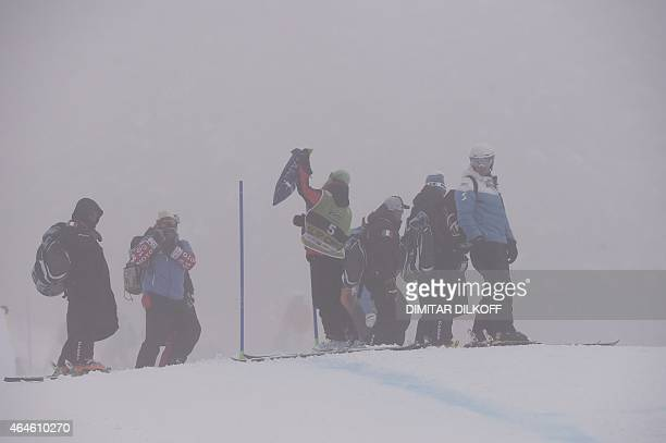 A race marshall removes a gate on the slope after the Fis Alpine Ski World Cup women's Super G race was canceled due to heavy fog in Bansko on...