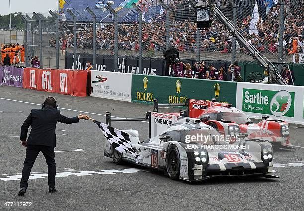 A race marshall waves the end of race black and white checkered flag as Germany's Nico Hulkenberg in his Porsche 919 Hybrid N°19 crosses the finish...