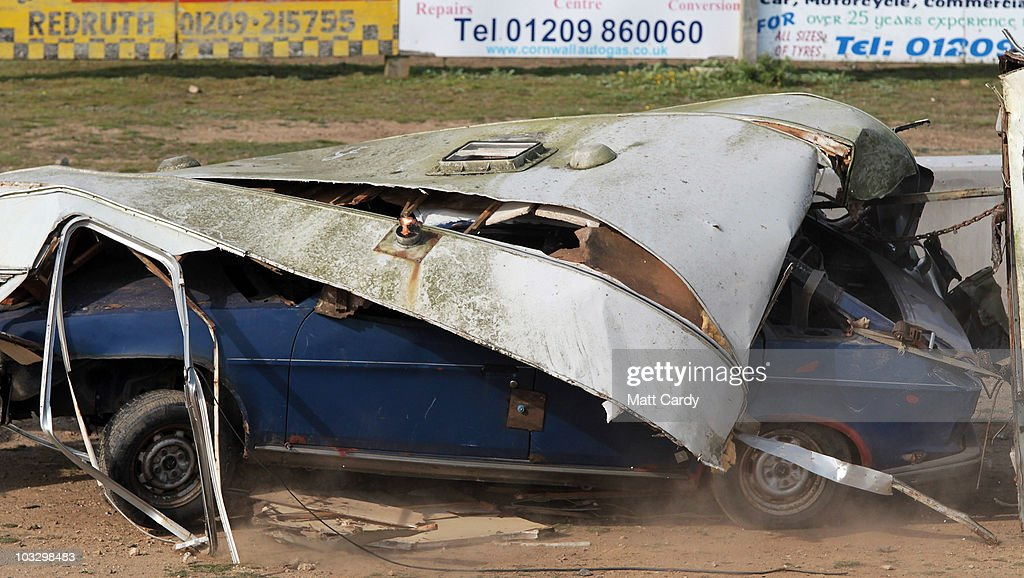Race marshalls try to move wreckage on a banger racers car that has been towing an old caravans as it competes in the annual Cornish Caravan Chaos at...