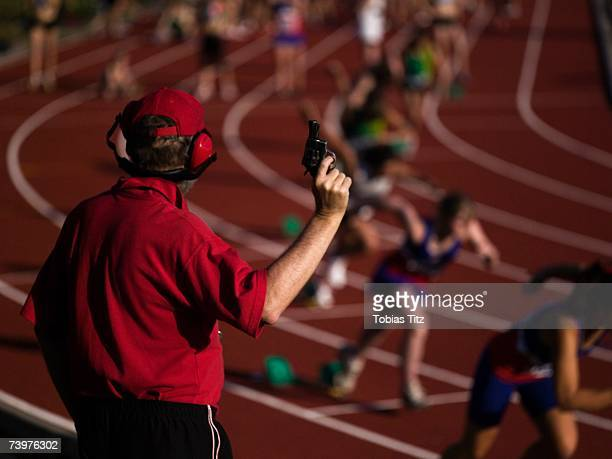 Race official holding a starting gun at the beginning of a track event