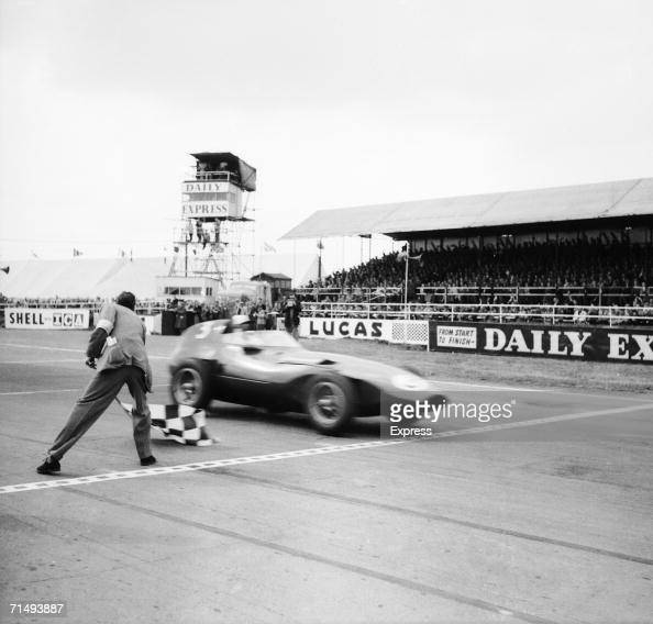 A race official waves Stirling Moss over the line with the chequered flag as he wins the Daily Express International Trophy driving the new Vanwall...
