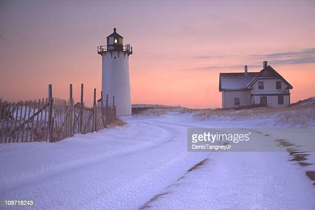 Race Point Lighthouse and House with Snowy Landscape at Sunset