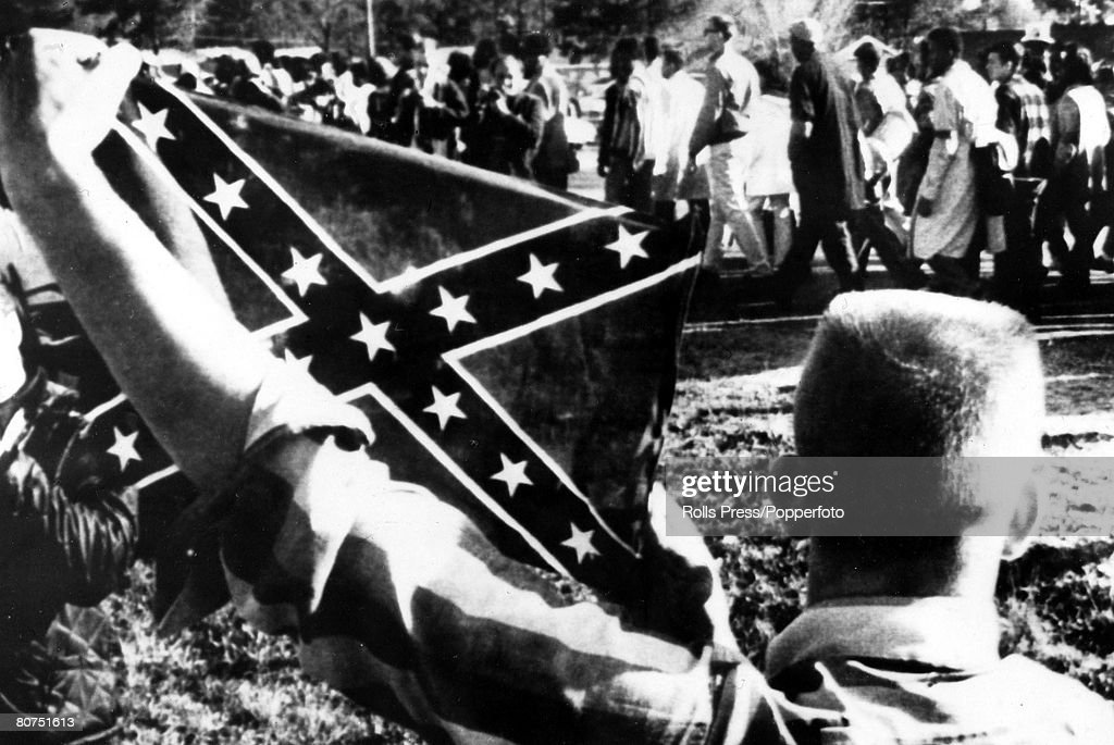 22nd March 1965, Selma, Alabama, A white youth holds up a Confederate flag to antagonise civil rights marchers as they walk along the highway