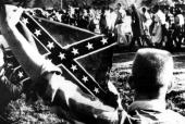22nd March 1965 Selma Alabama A white youth holds up a Confederate flag to antagonise civil rights marchers as they walk along the highway