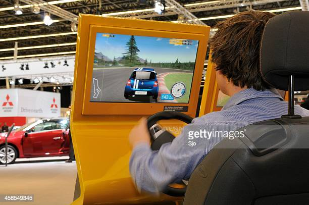 Race simulator with a man playing a racing computer game