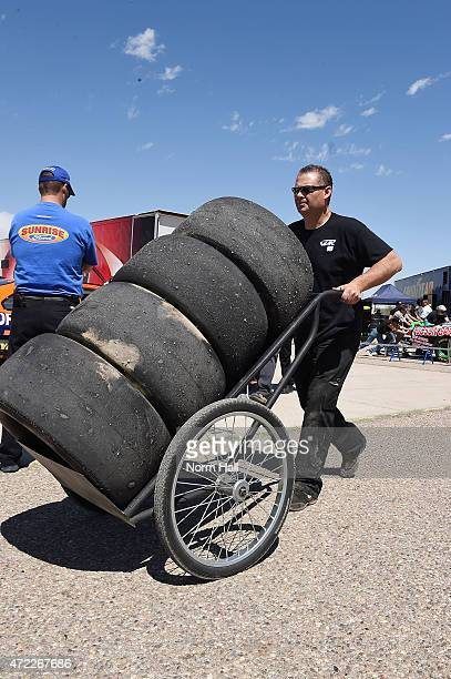 A race team crew member wheels some tires to his garage prior to the NASCAR KN Pro Series West race at Tucson Speedway on May 2 2015 in Tucson Arizona