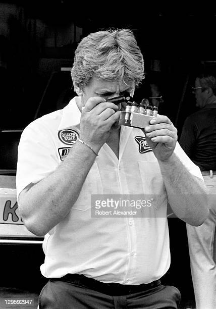 NASCAR race team owner and engine builder Robert Yates checks the gap on a set of spark plugs destined for driver Bobby Allison's car prior to...