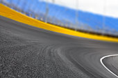 Empty race track at a motor speedway for motorsports at turn 1. Shallow dof.