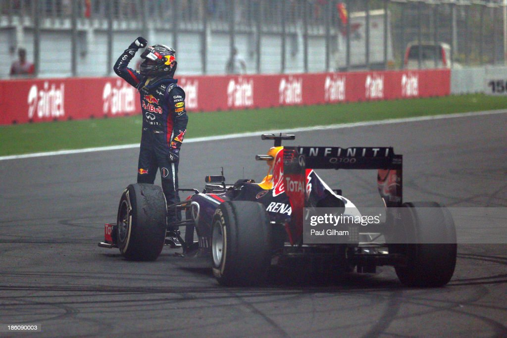 Race winner and 2013 Formula One World Champion <a gi-track='captionPersonalityLinkClicked' href=/galleries/search?phrase=Sebastian+Vettel&family=editorial&specificpeople=2233605 ng-click='$event.stopPropagation()'>Sebastian Vettel</a> of Germany and Infiniti Red Bull Racing celebrates in front of the crowd on the main straight following the Indian Formula One Grand Prix at Buddh International Circuit on October 27, 2013 in Noida, India.
