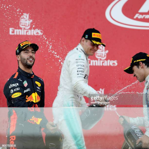 Race winner Daniel Ricciardo of Australia and Red Bull Racing celebrates his win with sevcond placed Valtteri Bottas of Finland and Mercedes GP and...