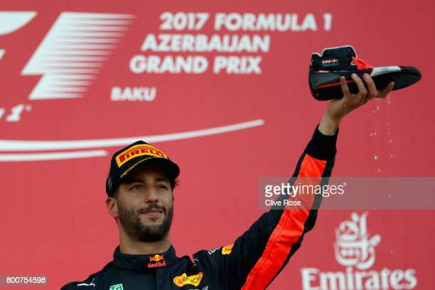 Race winner Daniel Ricciardo of Australia and Red Bull Racing celebrates his win on the podium with a shoey during the Azerbaijan Formula One Grand...