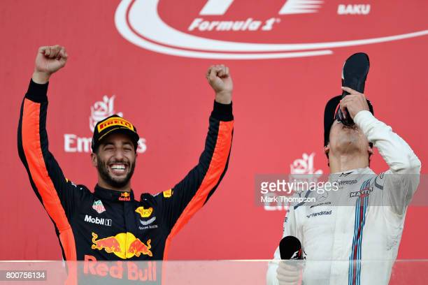 Race winner Daniel Ricciardo of Australia and Red Bull Racing celebrates his win on the podium with third placed finisher Lance Stroll of Canada and...