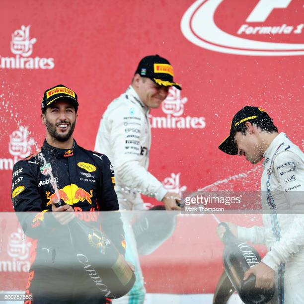 Race winner Daniel Ricciardo of Australia and Red Bull Racing celebrates his win with second placed Valtteri Bottas of Finland and Mercedes GP and...