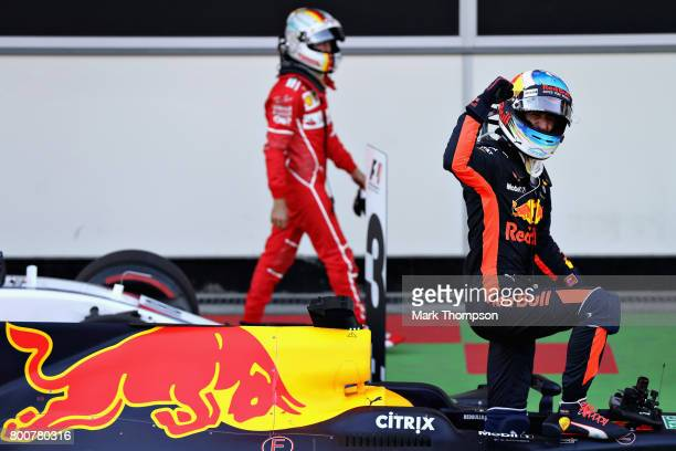 Race winner Daniel Ricciardo of Australia and Red Bull Racing celebrates his win in parc ferme as Sebastian Vettel of Germany and Ferrari walks past...
