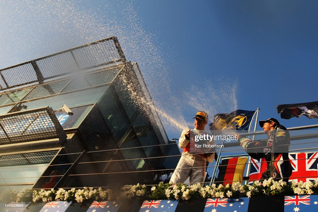 Race winner Jenson Button (L) of Great Britain and McLaren celebrates with second placed Sebastian Vettel (R) of Germany and Red Bull Racing on the podium following the Australian Formula One Grand Prix at the Albert Park circuit on March 18, 2012 in Melbourne, Australia.