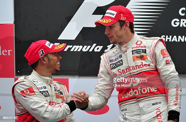 Race winner Jenson Button of Great Britain and McLaren Mercedes is congratulated on the podium by second placed team mate Lewis Hamilton of Great...