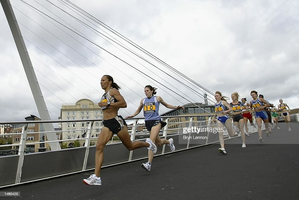 Race winner Kelly Holmes of Great Britain crosses the Gateshead Millennium Bridge during the BUPA Great North Mile on Newcastle Quayside, Newcastle, England on October 5, 2002. (Photo by Bryn Lennon/Getty Images).