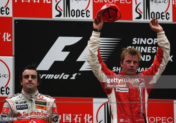 Race winner Kimi Raikkonen of Finland and Ferrari celebrates with second placed Fernando Alonso of Spain and McLaren Mercedes on the podium after...