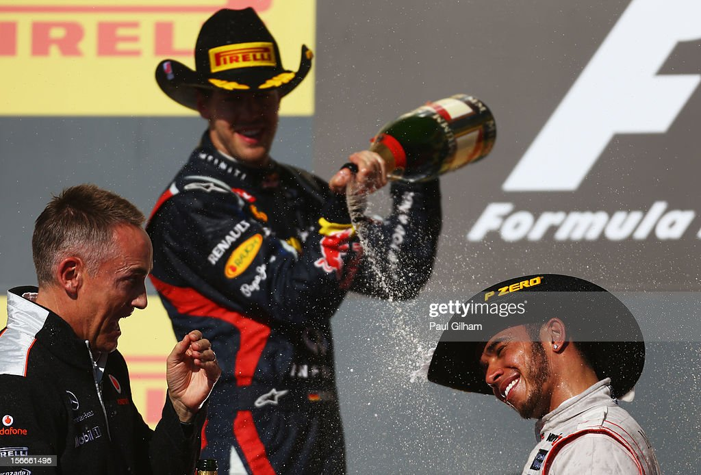 Race winner Lewis Hamilton (R) of Great Britain and McLaren celebrates on the podium alongside second placed Sebastian Vettel (C) of Germany and Red Bull Racing and his Team Principal Martin Whitmarsh (L) following the United States Formula One Grand Prix at the Circuit of the Americas on November 18, 2012 in Austin, Texas.