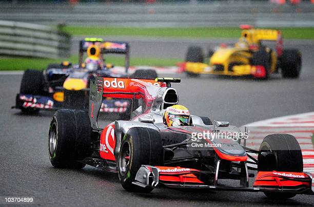 Race winner Lewis Hamilton of Great Britain and McLaren Mercedes leads from second placed Mark Webber of Australia and Red Bull Racing and third...