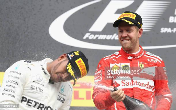 Race winner Lewis Hamilton of Great Britain and Mercedes GP and second place Sebastian Vettel of Germany and Ferrari celebrate on the podium during...