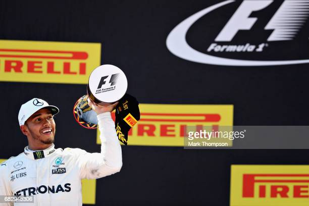 Race winner Lewis Hamilton of Great Britain and Mercedes GP celebrates his win on the podium during the Spanish Formula One Grand Prix at Circuit de...