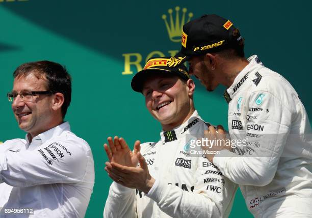 Race winner Lewis Hamilton of Great Britain and Mercedes GP celebrates his win on the podium with second place finisher Valtteri Bottas of Finland...