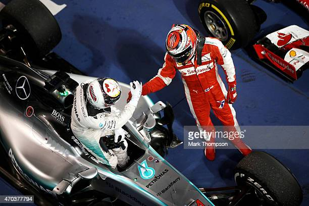 Race winner Lewis Hamilton of Great Britain and Mercedes GP is congratulated by Kimi Raikkonen of Finland and Ferrari in Parc Ferme following the...