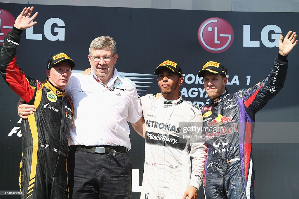Race winner Lewis Hamilton of Great Britain and Mercedes GP celebrates on the podium with second placed Kimi Raikkonen of Finland and Lotus third...