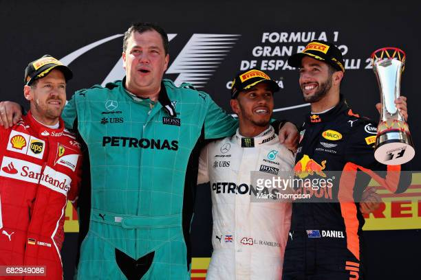 Race winner Lewis Hamilton of Great Britain and Mercedes GP celebrates on the podium with second placed finisher Sebastian Vettel of Germany and...