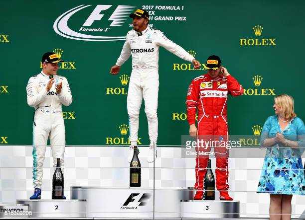 Race winner Lewis Hamilton of Great Britain and Mercedes GP celebrates on the podium with second placed Valtteri Bottas of Finland and Mercedes GP...