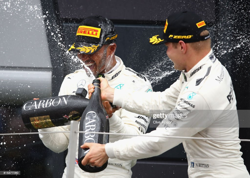 Race winner Lewis Hamilton of Great Britain and Mercedes GP celebrates on the podium with Valtteri Bottas of Finland and Mercedes GP during the Formula One Grand Prix of Great Britain at Silverstone on July 16, 2017 in Northampton, England.