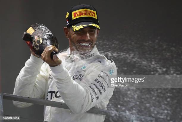 Race winner Lewis Hamilton of Great Britain and Mercedes GP celebrates on the podium during the Formula One Grand Prix of Singapore at Marina Bay...