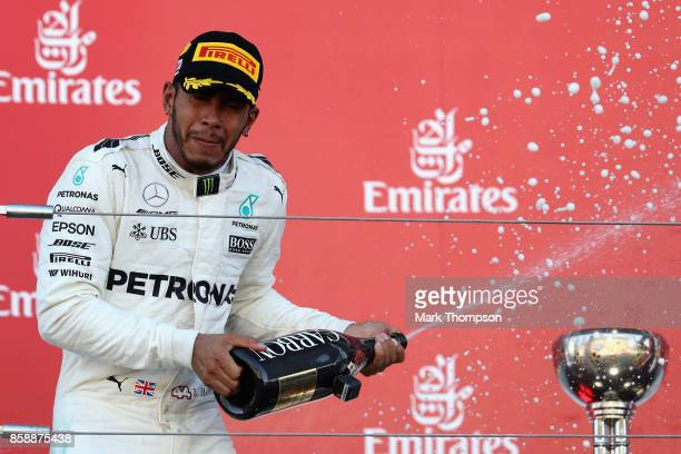 Race winner Lewis Hamilton of Great Britain and Mercedes GP celebrates on the podium during the Formula One Grand Prix of Japan at Suzuka Circuit on...