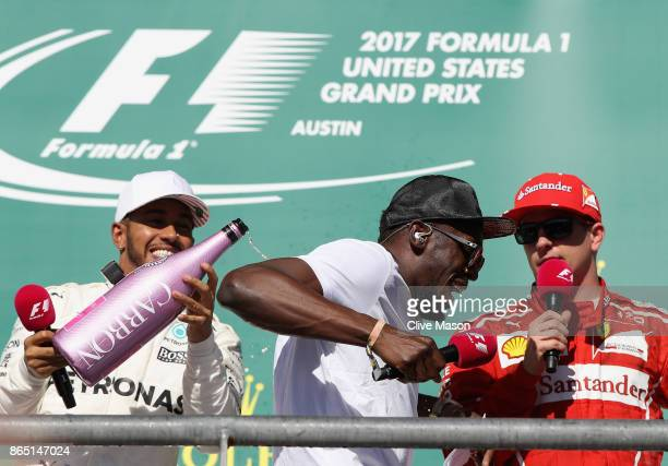 Race winner Lewis Hamilton of Great Britain and Mercedes GP celebrates on the podium with sprinting legend Usain Bolt and Kimi Raikkonen of Finland...